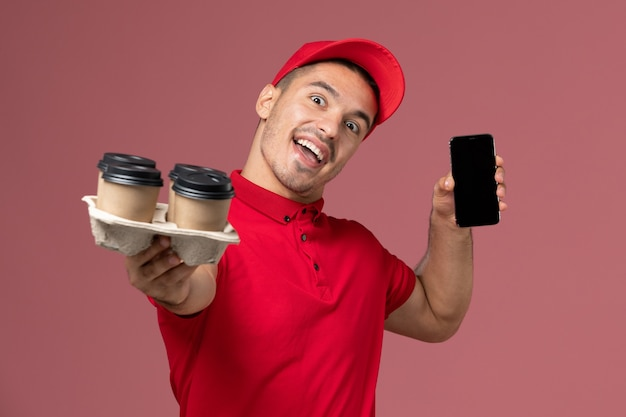 Front view male courier in red uniform and cape holding delivery coffee cups with phone on the pink wall
