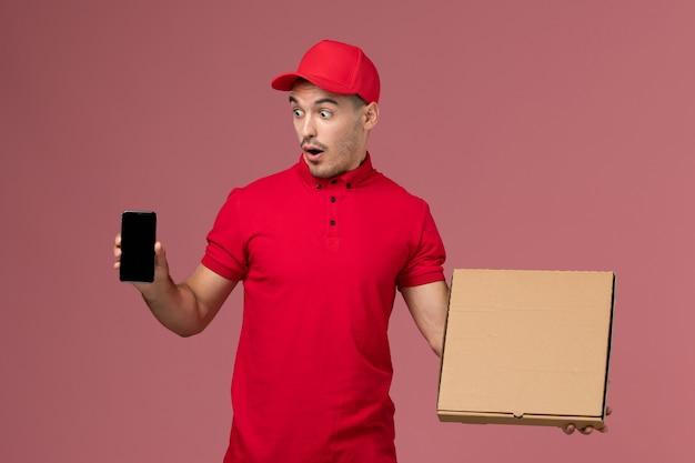 Corriere maschio di vista frontale in uniforme rossa e mantello che tiene la scatola di cibo insieme al telefono sull'uniforme di consegna maschile di lavoro di servizio da parete rosa