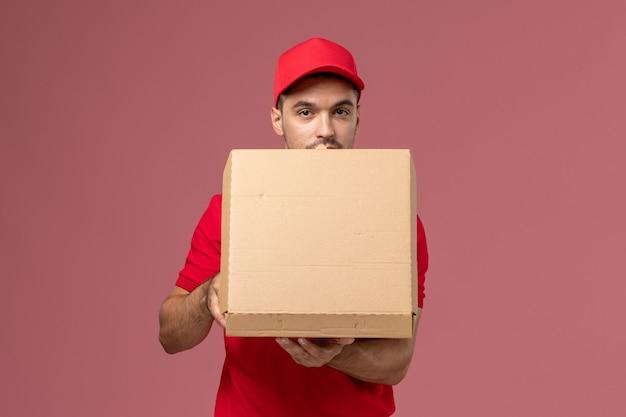 Corriere maschio di vista frontale in uniforme rossa e mantello che tiene la scatola di cibo aprendolo sul lavoro di lavoratore scrivania rosa chiaro