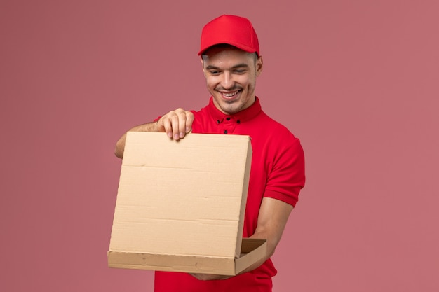 Front view male courier in red uniform and cape holding food box and opening it on light-pink wall worker job