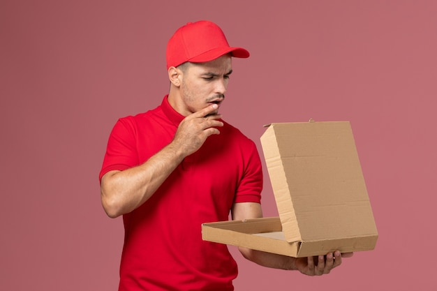 Front view male courier in red uniform and cape holding food box thinking on light-pink wall worker
