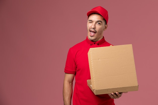 Front view male courier in red uniform and cape holding food box winking on light-pink wall worker