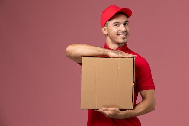 Corriere maschio di vista frontale in uniforme rossa e mantello che tiene scatola di cibo con un sorriso sul lavoro di operaio muro rosa