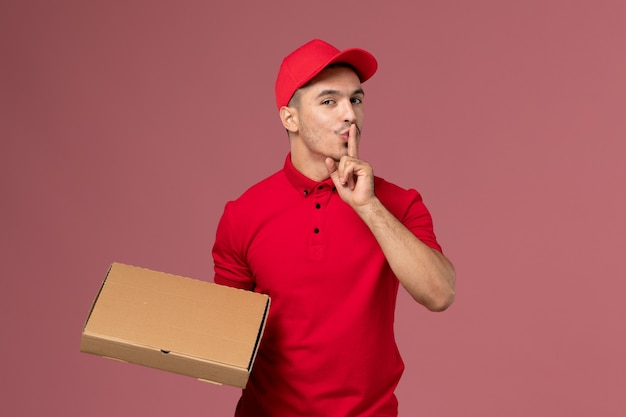 Front view male courier in red uniform and cape holding food delivery box showing silence sign on pink desk delivery uniform worker job
