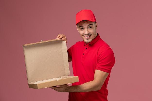 Corriere maschio di vista frontale in uniforme rossa e contenitore di consegna del cibo della tenuta del capo che sorride sul lavoratore uniforme maschio di consegna di servizio della parete rosa