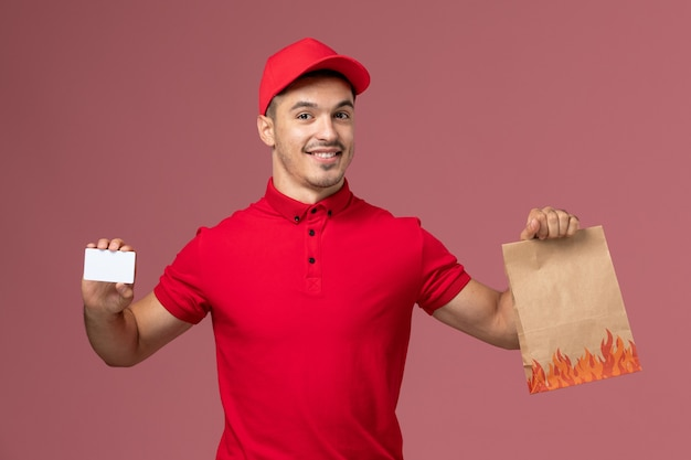 Front view male courier in red uniform and cape holding food package and card on the pink wall job