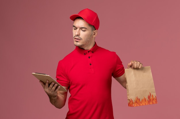 Front view male courier in red uniform and cape holding food package and notepad reading it on pink wall service delivery worker job uniform