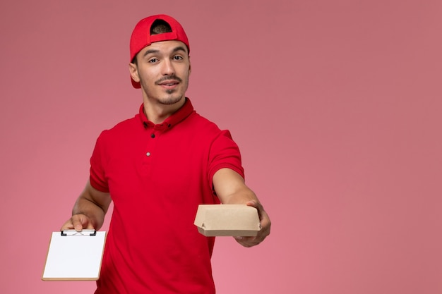 Front view male courier in red uniform and cape holding little delivery package with notepad writing note on pink background.