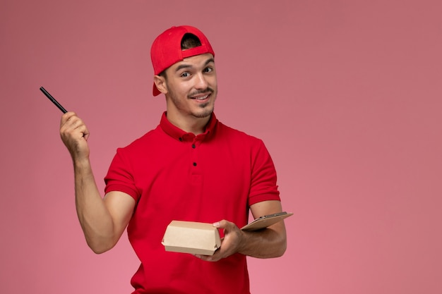 Front view male courier in red uniform and cape holding little delivery package with notepad writing note on the pink background.