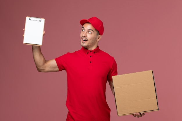 Corriere maschio di vista frontale in uniforme rossa e mantello che tiene blocco note e scatola di cibo sulla parete rosa