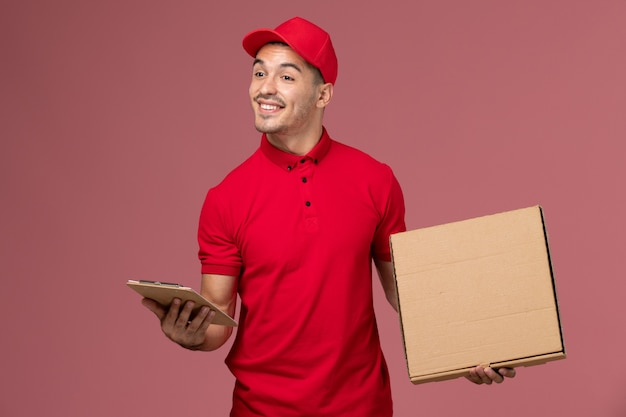 Front view male courier in red uniform and cape holding notepad food box with smile on the pink wall service job male delivery uniform