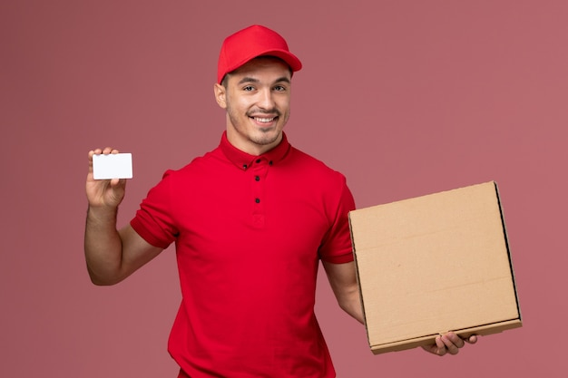 Front view male courier in red uniform and cape holding white card and food box on the pink wall service job male delivery uniform