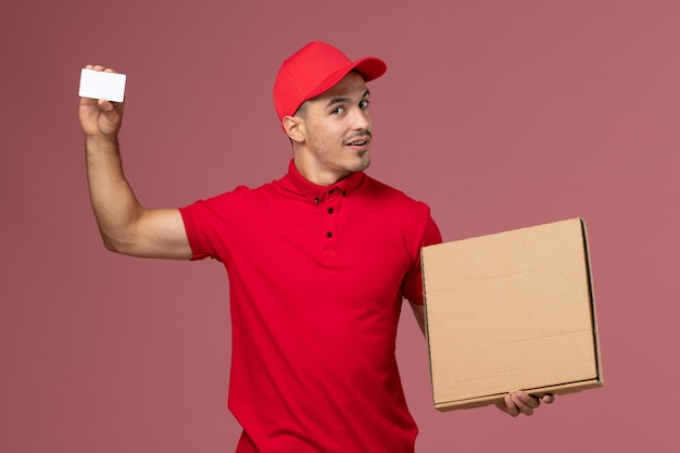 Front view male courier in red uniform and cape holding white card and food box on pink wall
