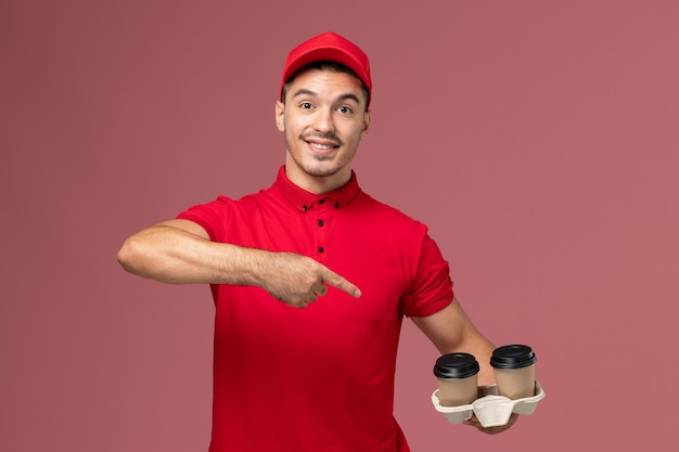 Front view male courier in red uniform holding brown delivery coffee cup on pink wall service delivery male uniform job