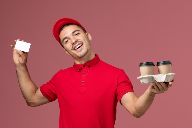 Front view male courier in red uniform holding brown delivery coffee cups and card on light pink wall worker work