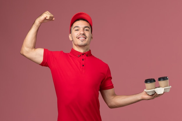 Corriere maschio di vista frontale in uniforme rossa che tiene le tazze di caffè marroni di consegna e che flette sul maschio rosa dell'operaio della parete