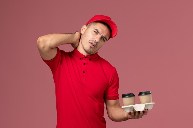 Front view male courier in red uniform holding brown delivery coffee cups naving neckache on pink desk  male worker