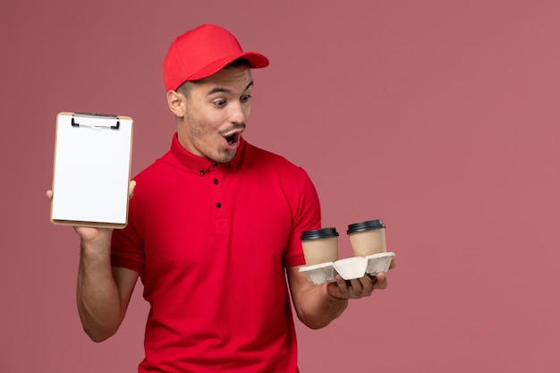 Front view male courier in red uniform holding brown delivery coffee cups and notepad on the light pink wall worker job male
