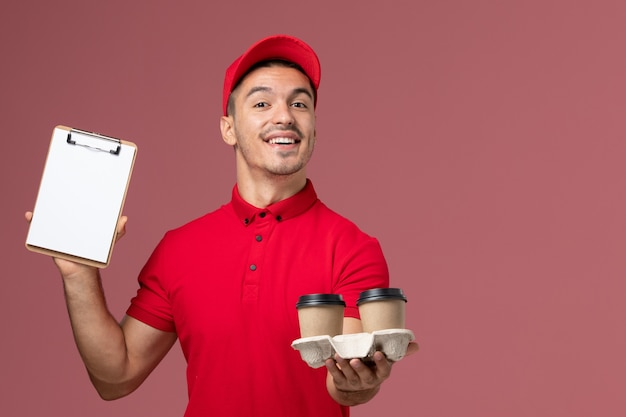 Front view male courier in red uniform holding brown delivery coffee cups and notepad with smile on pink wall worker