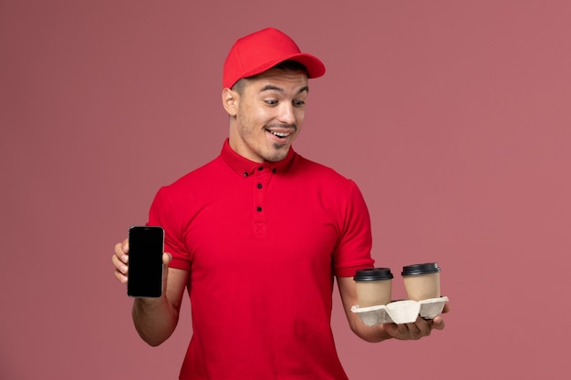 Front view male courier in red uniform holding brown delivery coffee cups and phone on the light-pink wall worker job