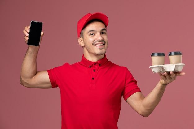 Corriere maschio di vista frontale in uniforme rossa che tiene le tazze di caffè e il telefono marroni di consegna sulla parete rosa-chiaro