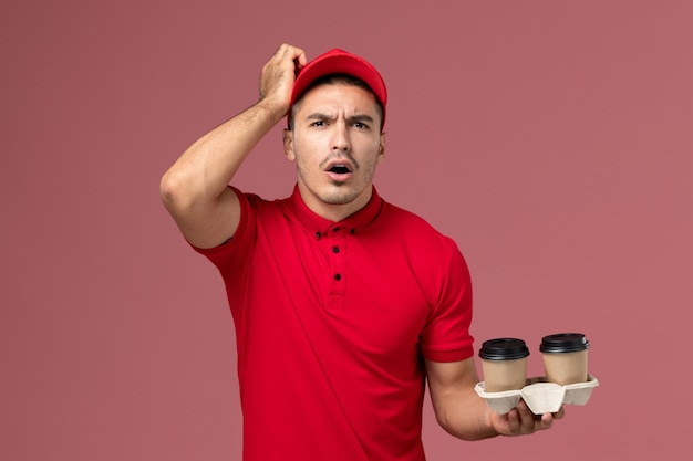Front view male courier in red uniform holding brown delivery coffee cups on the pink wall  male worker