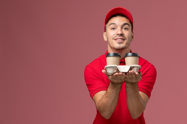 Front view male courier in red uniform holding brown delivery coffee cups on the pink wall  worker