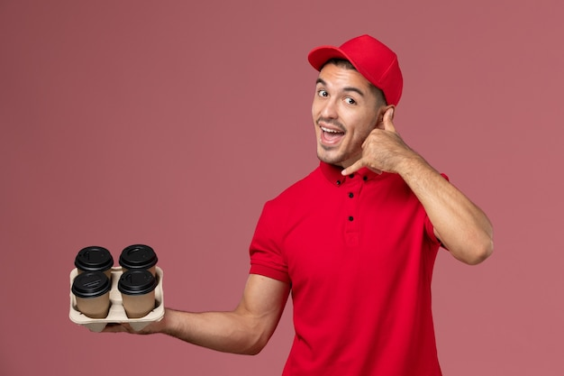 Front view male courier in red uniform holding brown delivery coffee cups posing on light pink wall