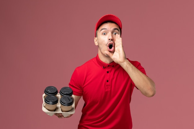 Front view male courier in red uniform holding brown delivery coffee cups screaming on light pink wall worker