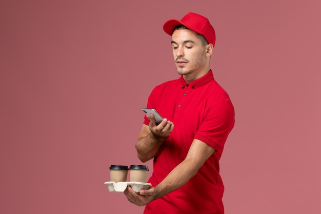Front view male courier in red uniform holding brown delivery coffee cups taking photo of them on the pink wall