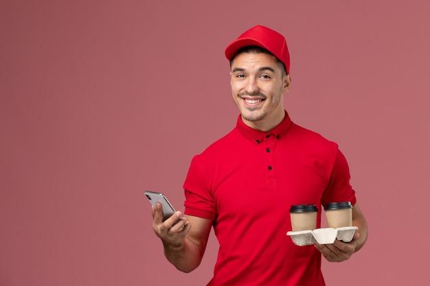 Corriere maschio di vista frontale in uniforme rossa che tiene le tazze di caffè marroni di consegna e che utilizza un telefono sulla parete rosa chiaro