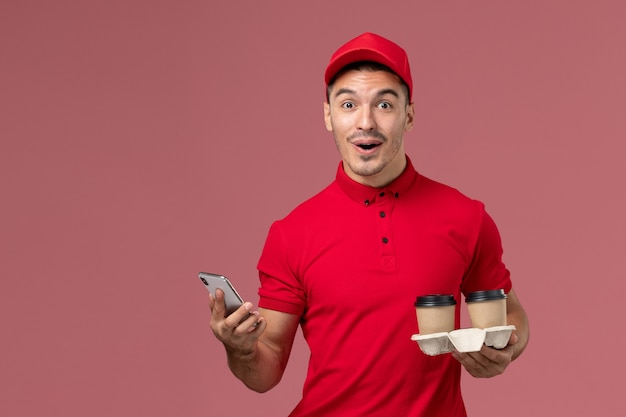 Front view male courier in red uniform holding brown delivery coffee cups and using a phone on the light pink wall