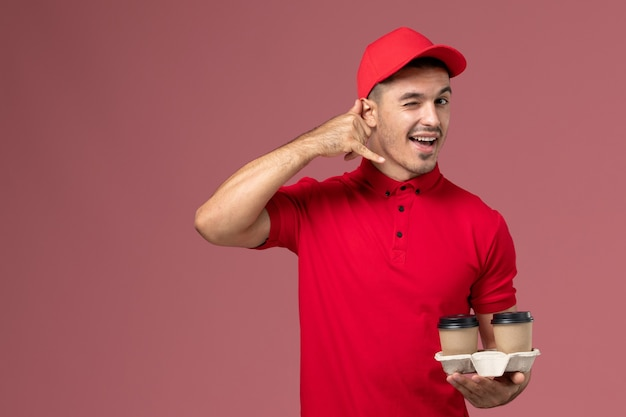 Front view male courier in red uniform holding brown delivery coffee cups winking on pink wall  worker male