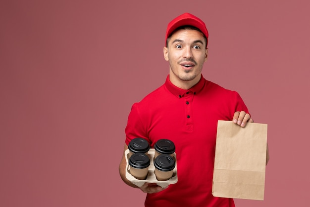 Front view male courier in red uniform holding brown delivery coffee cups with food package on pink desk service delivery job worker uniform