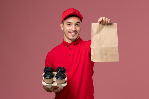 Front view male courier in red uniform holding brown delivery coffee cups with food package on the pink wall service delivery job worker uniform