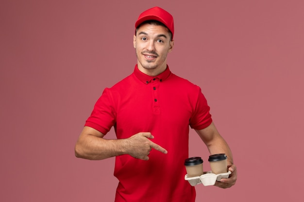 Front view male courier in red uniform holding brown delivery coffee cups with a slight smile on pink wall  male
