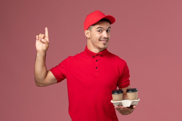 Front view male courier in red uniform holding brown delivery coffee cups with slight smile on pink wall  worker