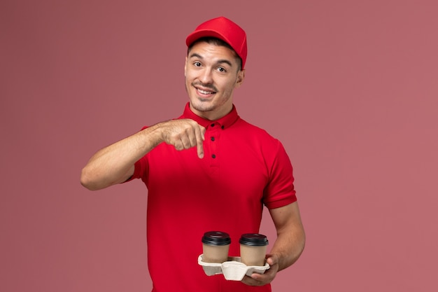 Front view male courier in red uniform holding brown delivery coffee cups with a smile on pink wall service delivery worker uniform job