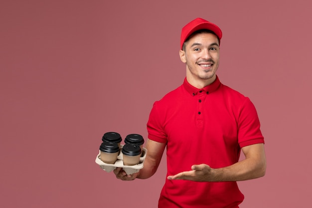 Front view male courier in red uniform holding brown delivery coffee cups with smile on pink wall worker
