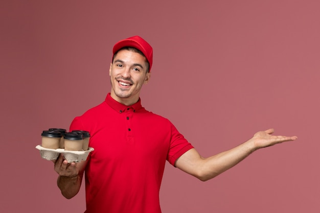 Front view male courier in red uniform holding brown delivery coffee cups with smile on the pink wall