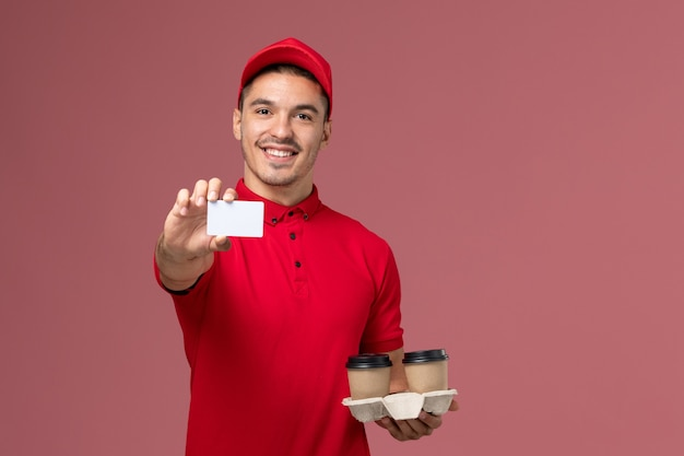 Front view male courier in red uniform holding brown delivery coffee cups with white card on light-pink wall