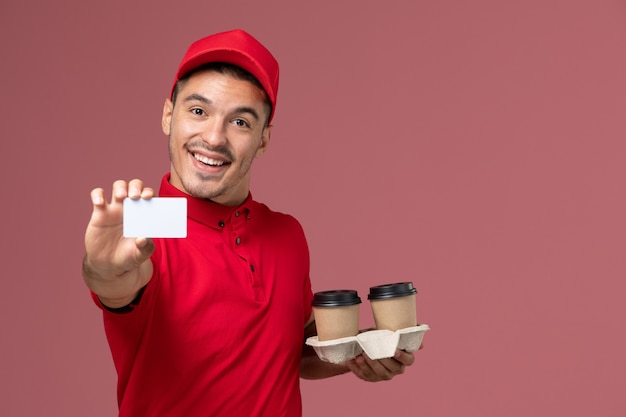 Front view male courier in red uniform holding brown delivery coffee cups with white card smiling on pink wall