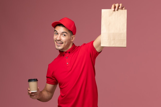 Front view male courier in red uniform holding delivery coffee cup and food package on pink wall service delivery worker male uniform job
