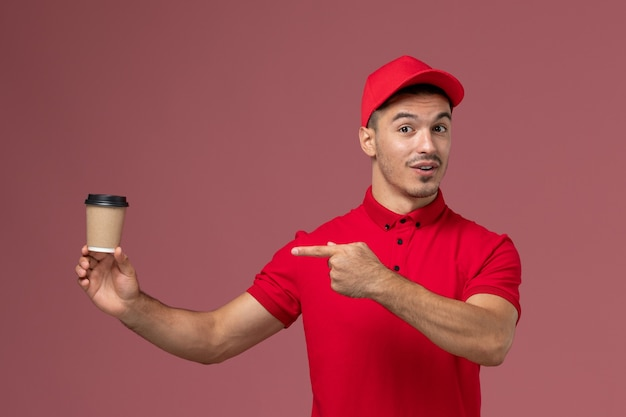 Front view male courier in red uniform holding delivery coffee cup on light-pink desk male worker
