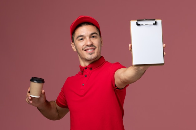 Front view male courier in red uniform holding delivery coffee cup and notepad smiling on the pink wall  worker male work