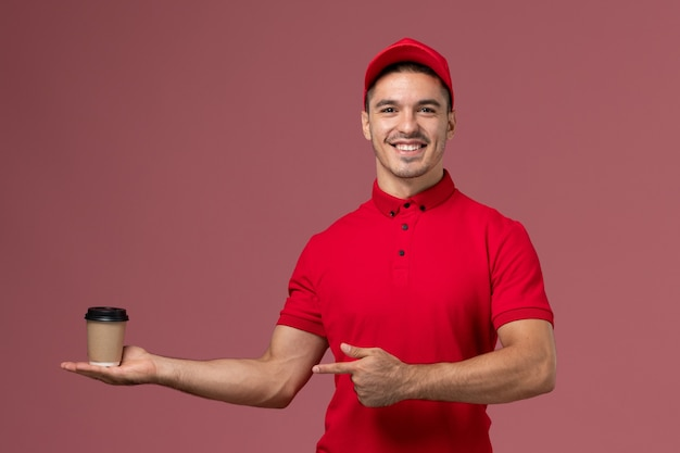 Front view male courier in red uniform holding delivery coffee cup on pink desk job male worker