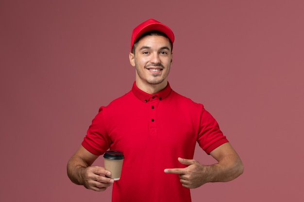 Front view male courier in red uniform holding delivery coffee cup on pink wall job male worker