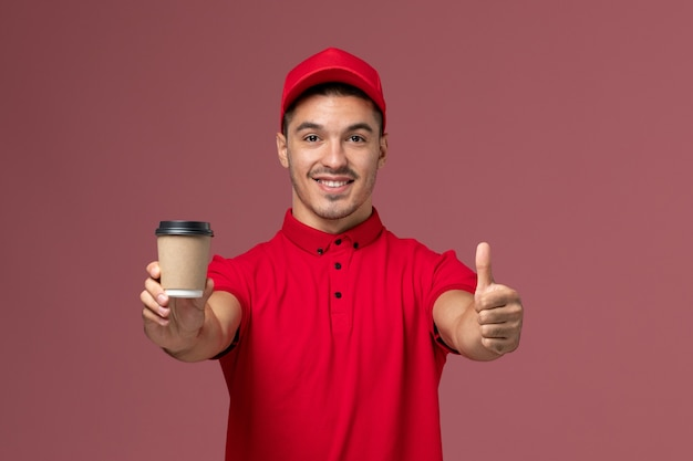 Front view male courier in red uniform holding delivery coffee cup on pink wall job