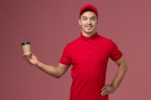 Front view male courier in red uniform holding delivery coffee cup on the pink wall job