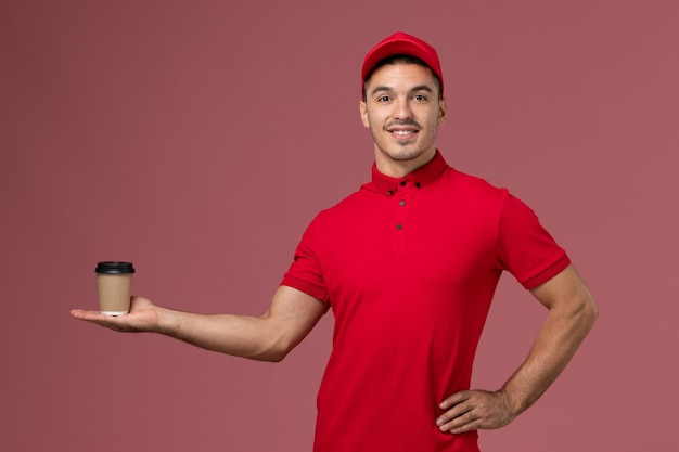 Front view male courier in red uniform holding delivery coffee cup on pink wall male worker